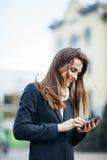 Счастливая женщина на улице города с sms сочинительства мобильного телефона Стоковое Изображение RF