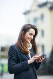 Счастливая женщина на улице города с sms сочинительства мобильного телефона Стоковые Фотографии RF