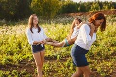 Счастливая женщина носит девушку на ее задней части лета в древесинах Стоковые Изображения RF
