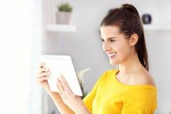 Счастливая женщина ослабляя дома с таблеткой Стоковые Изображения RF