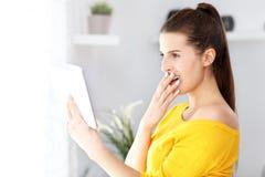 Счастливая женщина ослабляя дома с таблеткой Стоковое фото RF