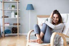Счастливая женщина отдыхая удобно сидеть на современном стуле в живущей комнате дома стоковая фотография rf