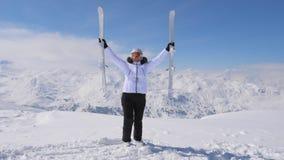 Счастливая женщина поднимает ее покатые лыжи на горной вершине стоковая фотография rf