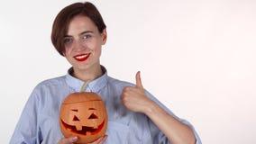 Счастливая женщина показывая большие пальцы руки вверх, держащ тыкву высекаенную хеллоуином стоковые изображения