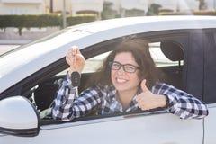 Счастливая женщина показывая большой палец руки вверх и управляя новым автомобилем Положительное выражение стороны стоковое фото rf