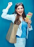 Счастливая женщина показывая pasport, кредитную карточку и билет на праздник стоковая фотография