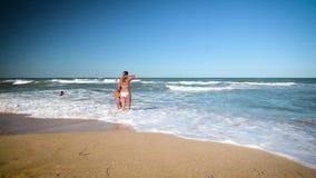 Счастливая женщина при дети брызгая на береге моря видеоматериал