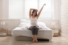 Счастливая женщина протягивая на кровати стоковые изображения rf
