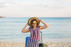 Счастливая женщина путешественника с чемоданом на пляже Концепция перемещения, путешествия, отключения Стоковое фото RF