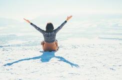 Счастливая женщина сидит на снежном холме горы над городом солнечно стоковое фото rf