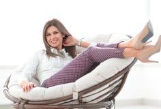 Счастливая женщина сидя в удобном стуле стоковая фотография