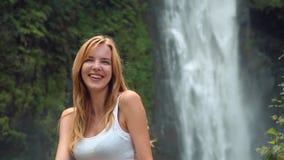 Счастливая женщина смеясь над перед водопадом видеоматериал