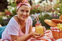 Счастливая женщина среднего возраста redhead в вскользь одеждах с держателем наслаждаясь во время пикника outdoors пока лежащ на  Стоковые Изображения