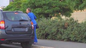 Счастливая женщина стоит и держит хозяйственные сумки Она усмехается Девушка развевает с рукой Позже тот автомобиль останавливал  видеоматериал