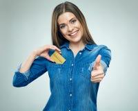 Счастливая женщина студента держа кредитную карточку и выставки thumb вверх Стоковые Изображения RF