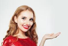 Счастливая женщина с пустой открытой рукой для рекламировать маркетинг или размещение продукта стоковое фото rf