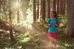 Счастливая женщина с рюкзаком идя на путь тропы в древесинах леса во время солнечного дня Группа в составе лето людей друзей стоковая фотография