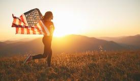 Счастливая женщина с флагом Соединенных Штатов наслаждаясь заходом солнца на na стоковые фото