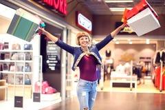 Счастливая женщина с хозяйственными сумками наслаждаясь на моле consumerism стоковое фото