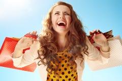 Счастливая женщина с хозяйственными сумками радуясь против голубого неба Стоковое фото RF
