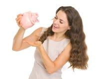 Счастливая женщина трястия вне чеканит от piggy банка Стоковая Фотография RF