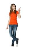Счастливая женщина указывая к стороне стоя в во всю длину Стоковое Фото