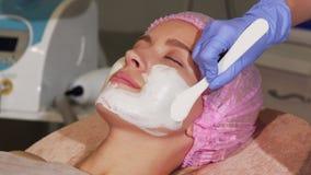 Счастливая женщина усмехаясь во время лицевого применения маски на салоне красоты сток-видео