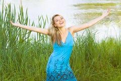 Счастливая женщина усмешки с естественной предпосылкой Стоковое Изображение