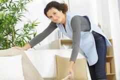 Счастливая женщина tidying грязная комната стоковое фото rf
