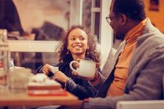 Счастливая жизнерадостная девушка смотря ее отца пока ел завтрак стоковое изображение rf