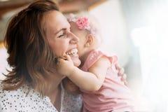 Счастливая жизнерадостная семья Мать и младенец целуя и обнимая Стоковое фото RF