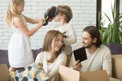 Счастливая жизнерадостная семья распаковывая коробки упаковки совместно, двигающ I Стоковая Фотография RF