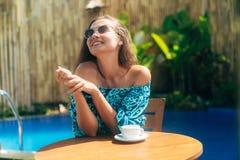 Счастливая загоренная девушка в солнечных очках сидит outdoors на таблице с чашками кофе или чаем стоковая фотография rf
