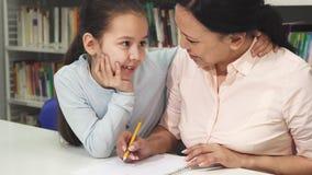 Счастливая зрелая азиатская женщина помогая ее маленькой дочери с изучать стоковая фотография rf