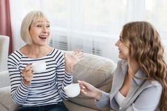 Счастливая зрелая мать и кофе и говорить дочери выпивая стоковая фотография rf