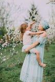 Счастливая игра мамы с дочерью на парке весны стоковые изображения