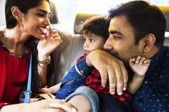 Счастливая индийская семья сидя в автомобиле стоковое изображение