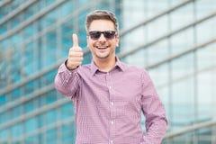 Счастливая исполнительная власть в солнечных очках показывая большие пальцы руки вверх outdoors стоковые фотографии rf