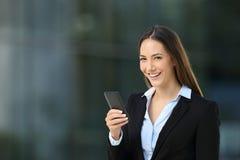 Счастливая исполнительная власть используя телефон и смотрящ камеру Стоковое фото RF