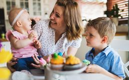 Счастливая и любящая мать и ее дети подготавливая домашнее украшение Стоковое Изображение