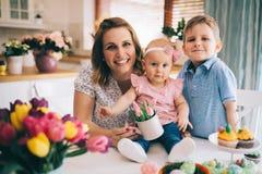 Счастливая и любящая мать и ее дети подготавливая домашнее украшение Стоковые Изображения
