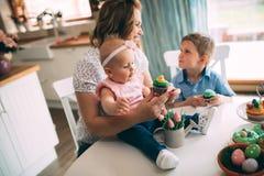 Счастливая и любящая мать и ее дети подготавливая домашнее украшение Стоковое Фото
