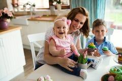 Счастливая и любящая мать и ее дети подготавливая домашнее украшение Стоковое Изображение RF