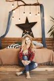 Счастливая и модная белокурая модельная девушка с очаровательной улыбкой в красной рубашке шотландки и в джинсах сидит около дере стоковые изображения rf