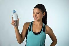 Счастливая и привлекательная латинская женщина спорта в фитнесе одевает держать усмехаться питьевой воды бутылки свежий и жизнера Стоковые Фотографии RF