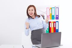 Счастливая и успешная коммерсантка поднимая ее оружия на предпосылке офиса и празднуя успех изолированный на белизне Насмешка вве Стоковые Фотографии RF