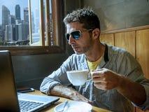 Счастливая и успешная молодая работа бизнесмена ослабленная от кофейни интернета с ноутбуком и мобильным телефоном делом стоковое изображение