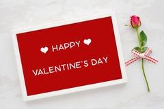 Счастливая карточка дня ` s валентинки в белых деревянных fram и красной розе дальше Стоковые Фото