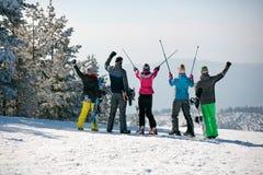 Счастливая катаясь на лыжах группа на верхней части горы задний взгляд Стоковые Изображения RF