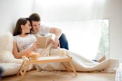 Счастливая книга лежать и чтения беременной женщины на кровати с супругом Стоковые Изображения RF